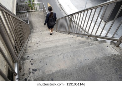 single asian young female in dark blue student uniform with black backpack walking down concrete stairs of overpass, back view of student that walk home after school