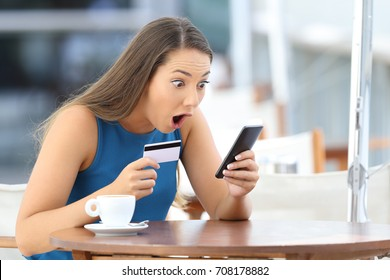 Single astonished buyer holding phone and credit card finding a good offer on line sitting in a restaurant