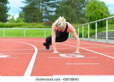 Single athletic mature woman in black jump suit doing hip warming up and stretching exercises on red racing track outdoors