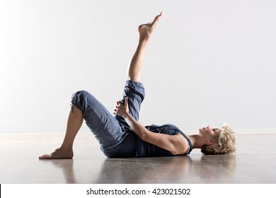 Single athletic woman with blond hair in blue outfit on back stretching hamstring muscles for leg in mid air