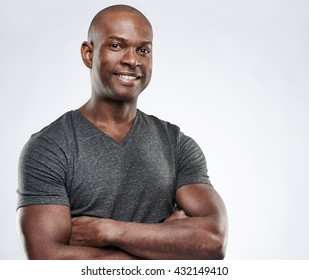 Single attractive smiling Black man in short sleeve workout shirt with folded muscular arms looking ahead with copy space over gray background