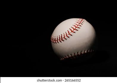 A single baseball on a black backdrop with single light illuminating it for isolation and drama.