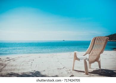 single beach chairs on tropical ocean beach
