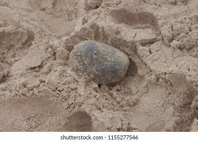 Single beach pebble and sand