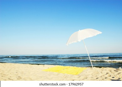 Single beach umbrella and towel on sand by sea in idyllic summer scene
