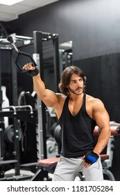 Single bearded adult male bodybuilder pulling black ring attached to machine off camera with one hand