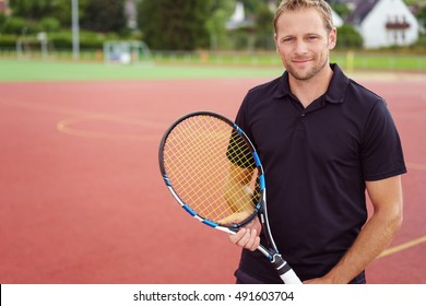 Single bearded handsome man holding tennis racket while standing near athletic track outdoors