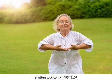 Single beautiful senior woman in white rolled up long sleeve blouse practicing breathing exercises outside with eyes closed on green grass with copy space