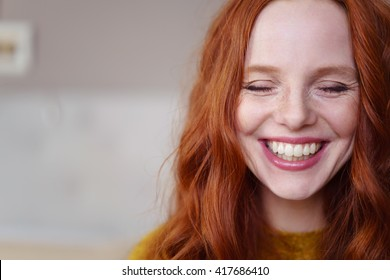 Single beautiful young Caucasian woman with long red hair and closed eyes next to copy space
