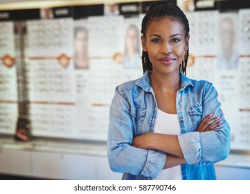 Single beautiful young woman with confident expression in rolled up sleeves in front of display and posters at store