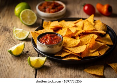 Single big black plate of yellow corn tortilla nachos chips with salsa sauce over wooden table
