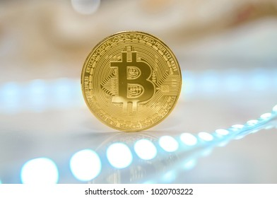 Single bitcoin coin or icon standing in sharp focus on a reflective surface with gold colored background to illustrate bitcoin exchange, mining or blockchain technology for cryptocurrency
