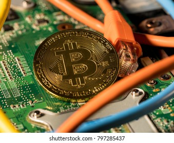 Single bitcoin coin standing on the motherboard of modern laptop computer