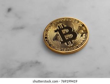 Single Bitcoin on marble surface