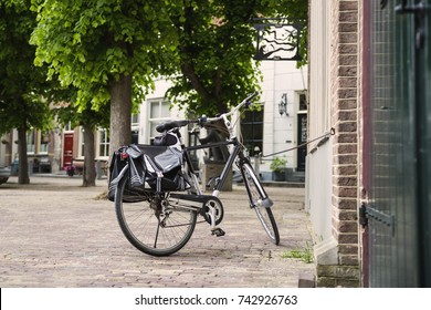 A single black bicycle is parked on a sidewalk of a historic city street,