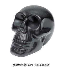 Single black human skull, plastic model, souvenir, isolated on white background