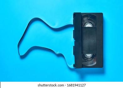 Single black old plastic vhs video cassette lies on blue desk. Concept of 90s. Flat lay. Close-up
