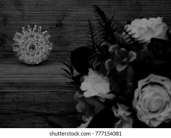 A Single Black and White Large Diamond Showing the Facet Cut of the Gem Stone, with a Foreground Blurred Flower Arrangement