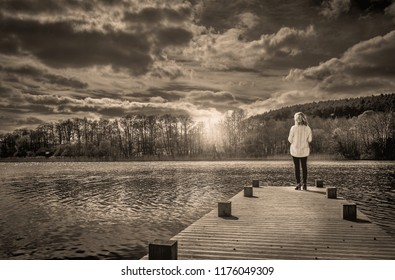 Single blonde woman in knitted cardigan standing on jetty looking out over a lake at sunset with dramatic sky and an evening atmosphere.