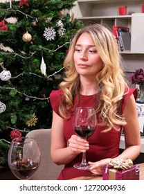 Single blonde woman in a red dress, celebrates Christmas with her husband. Sad human feelings during important winter holidays. Lonely life idea. Desaturated colors with no contrast. Close up shot