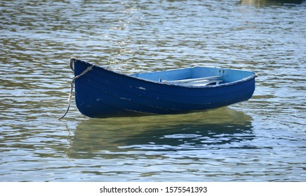 Single blue dinghy floating on water
