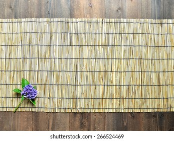 Single blue hydrangea on bamboo blind background.Image of Japanese style interior on  early summer