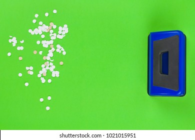 Single blue metal mechanical hole puncher and lot of round white confetti on blank green paper. Top view