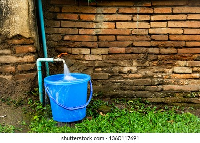 Single blue plastic bucket with running water tap on the green grass with the old brick wall background.