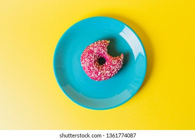 A single blue plate on a yellow background with a pink frosted sugar bomb doughnut with a bite mark, in it