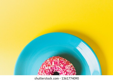 A single blue plate on a yellow background with a pink frosted sugar bomb doughnut in it, showing only the upper half of the plate