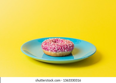A single blue plate on a yellow background with a pink frosted sugar bomb doughnut in it