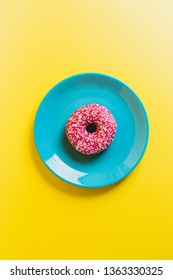A single blue plate on a yellow background with a pink frosted sugar bomb doughnut