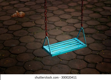 Single blue swing empty people and doll at dark night