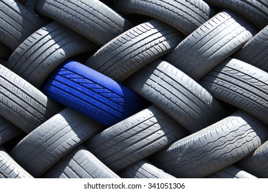 Single blue tire in a stack of tires