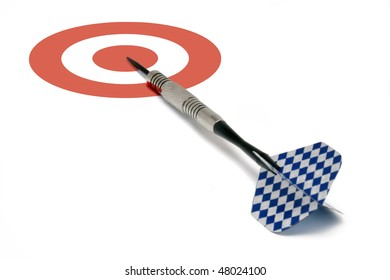 A single blue and white finned dart laying on a red and white bull's-eye target.  Conceptual business image for being 'on target', 'moving forward', etc.