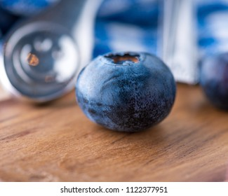 A single blueberry on a wooden surface in intentional shallow depth of field