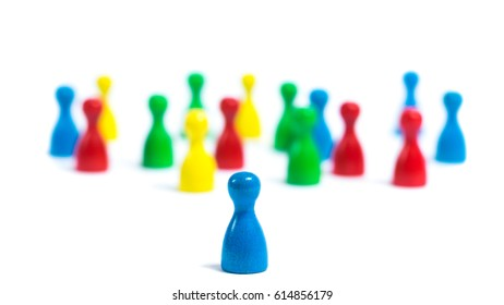 Single board game figure standing in the front, big group of individuals in the back. Symbol of leadership
