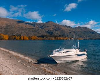 Single boat on Lake Wanaka at Roys Bay, Wanaka town, New Zealand