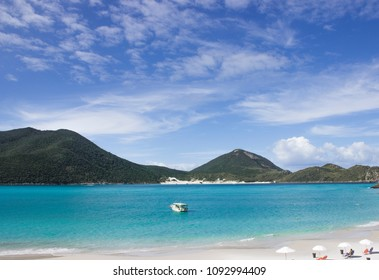 Single Boat in Tropical beach with transparent blue water and mountains in Arraial do Cabo, Brazil.