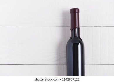 Single Bottle of Wine on a White Wood Table. The thin bottle has a wax seal over the top.
