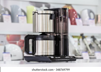 Single brand new metallic shiny drip coffee maker at retail store shelf, defocused background