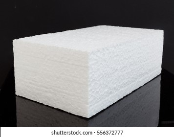 Single brick block of white styrofoam on black background. Horizontal.