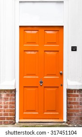Single bright orange painted wooden door with red brickwork and white walls