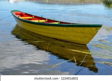 A single bright yellow wooden dory floats in a pond under blue sky and clouds. The boat has green trim with a red interior.  The blue sky and clouds are reflecting in the calm water.