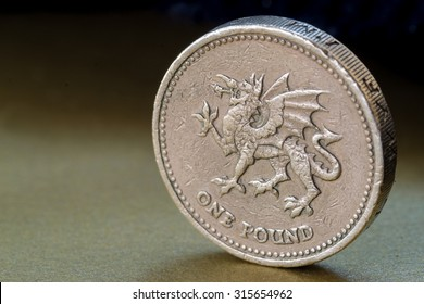 Single British pound Coin with imprinted Welsh Dragon standing upright on a graduated golden background