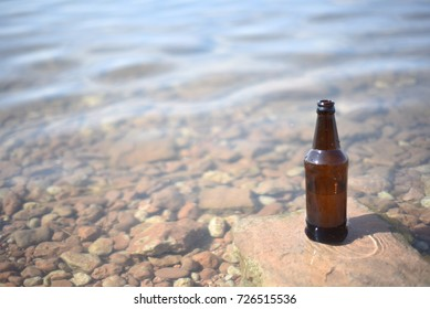 Single brown glass bottle with a rippling water background and natural sunlight