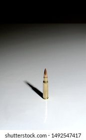 A single bullet (7.62 x 51 mm NATO) standing on a white surface with a gradient to black background. Plenty of negative space.