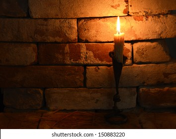 Single burning candle on the brick background in night