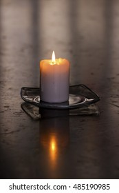 A single burning candle on a glass plate on top of a big polished stone table in a church
