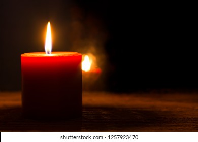 Single burning red candle and flame reflection in the dark window. Concept of Christmas Season, memory, condolence, hope